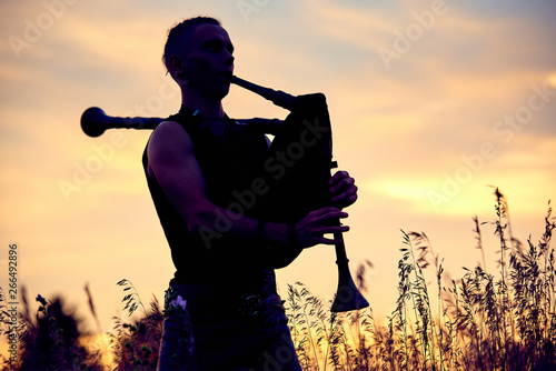 Stampa su Tela A young modern man plays musical bagpipes outside. Siluet