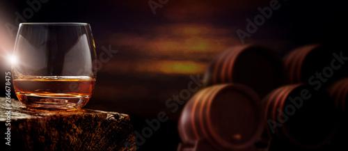 Fotografia Glas Whisky vor Fässern in Brennerei