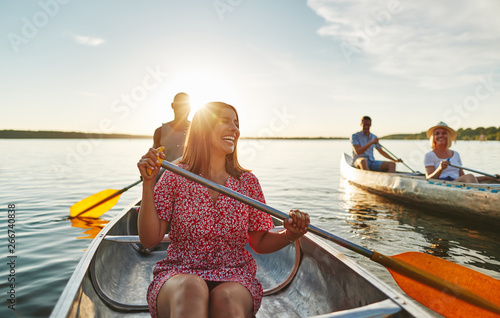 Laughing woman canoeing with friends on a late summer afternoon Fototapet