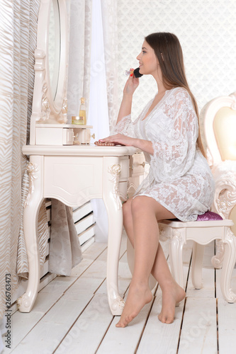 Tableau sur Toile Portrait of young woman sitting at dressing table