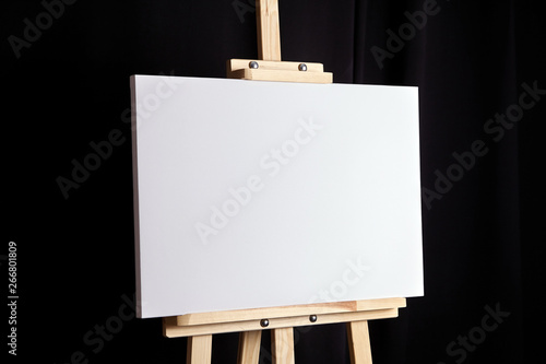 White blank canvas stands on a wooden artistic easel on black curtain background Fototapeta