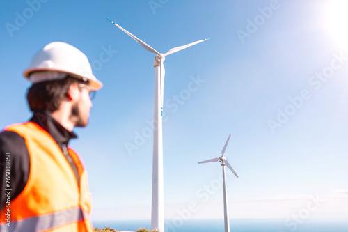 Giovane ingegnere con gilet ad alta visibilità, casco bianco e progetto in mano, sta controllando l'impianto eolico formato da turbine a vento in montagna Fototapeta