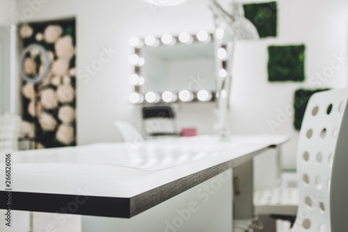Makeup artist's workplace a mirror with lamps on a white wall and a wooden armch Fototapete