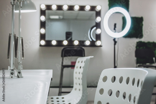 Leinwand Poster Makeup artist's workplace a mirror with lamps on a white wall and a wooden armch