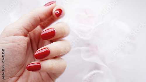 Photo Beautiful female hand with red nails against the background of a white wedding b