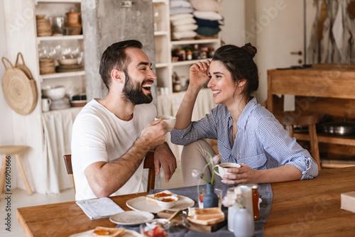 Billede på lærred Image of modern brunette couple eating breakfast together while sitting at table