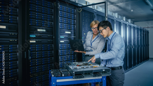 Fotografia In the Modern Data Center: Engineer and IT Specialist Work with Server Racks, on a Pushcart Equipment for Installing New Hardware