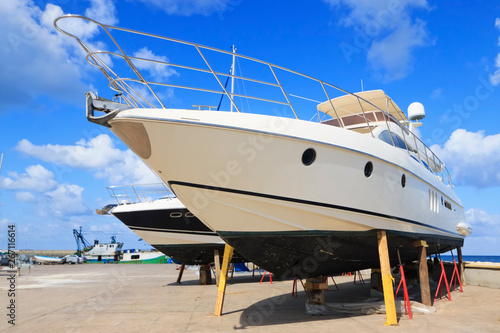 Fotografija Luxury motor yacht beached on a dry dock for painting and repair