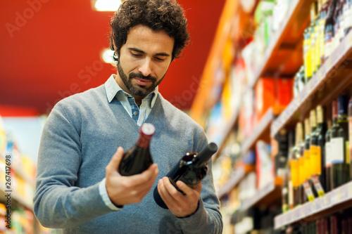 Photo Man in a supermarket choosing a wine
