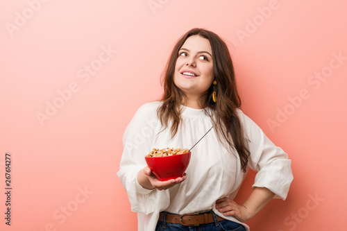 Foto Young plus size curvy woman holding a cereals bowl smiling confident with crossed arms