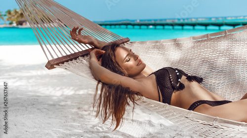 Canvas Print Woman relaxing in the hammock on tropical beach, summer vaction