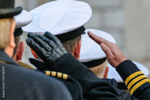 Canvas Print Royal Navy officers salute during Remembrance Day commemorations.