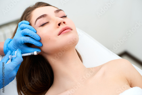 Beautician doctor with filler syringe making injection to jowls Fototapeta