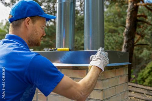 Billede på lærred tinsmith on the roof installing tin cap on the brick chimney