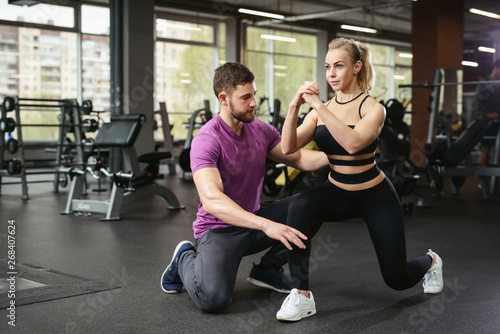 Fotografie, Tablou Sporty girl doing squats exercises with assistance of her personal trainer at public gym