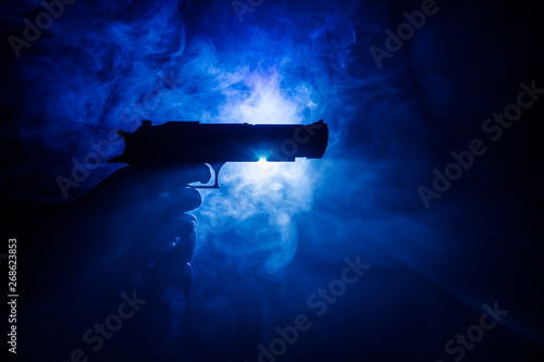 Canvas Print Male hand holding gun on black background with smoke toned back lights