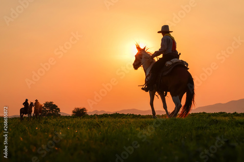 Murais de parede The silhouette of three men wearing a cowboy dress with horses and guns held in