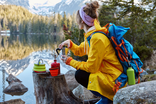 Outdoor view of young woman uses tourist equipment for making coffee, has portable gas stove on stump, focused in distance, admires scenic lakescape, rock mountains reflect in water Fototapete