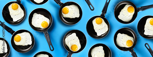 Fotografia Creative food pattern with fried eggs on pans over blue background