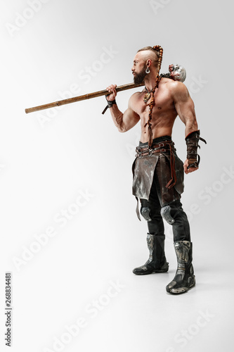 Obraz na plátně Serious long hair and muscular male model in leather viking's costume with the big mace cosplaying isolated on white studio background