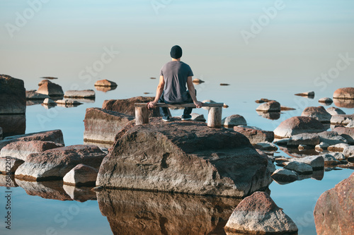 Obraz na plátně A man sits on a wooden bench and admires the complete calm of the sea