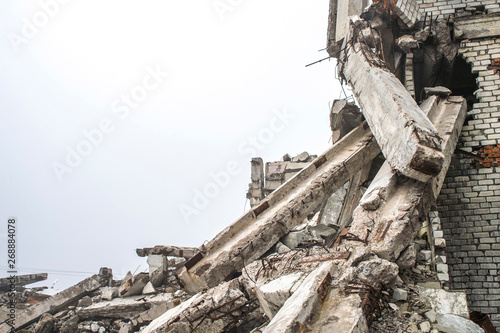 Fototapeta A huge pile of gray concrete debris from piles and stones of the destroyed building