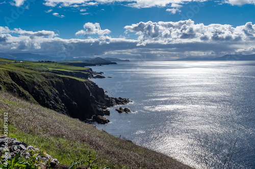 Fotografie, Tablou Looking along the rugged cliffs of the Dingle Peninsula, Ireland, bright blue sk