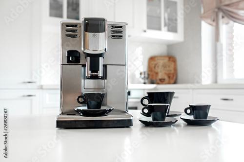 Fotografija Coffee machine with cups for espresso on the kitchen table
