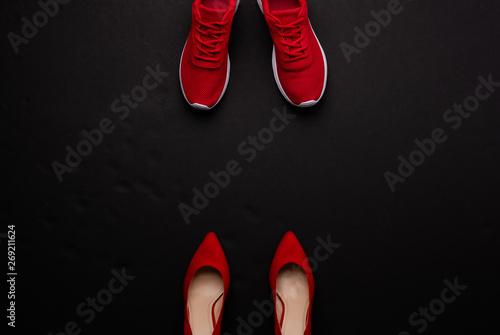 Obraz na plátne A studio shot of pair of running vs high heel shoes on black background