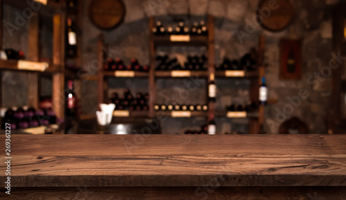 Leinwand Poster Defocused dark wine cellar background with wooden table in front
