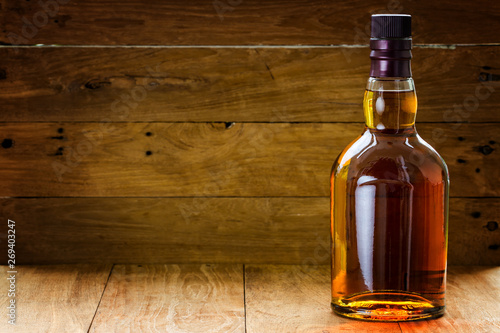 Fotografija bottle and glass of whiskey  on a wooden background made with vintage tones