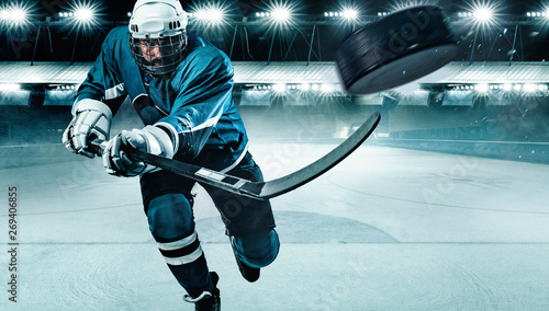 Obraz na płótnie Ice Hockey player athlete in the helmet and gloves on stadium with stick