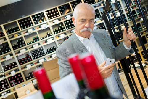 Photo man in a supermarket comparing two wine bottles