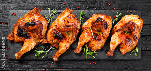 Tableau sur Toile Halves of appetizing grilled juicy chicken with golden brown crust served with lemon slices,barbeque  sauce and rosemary