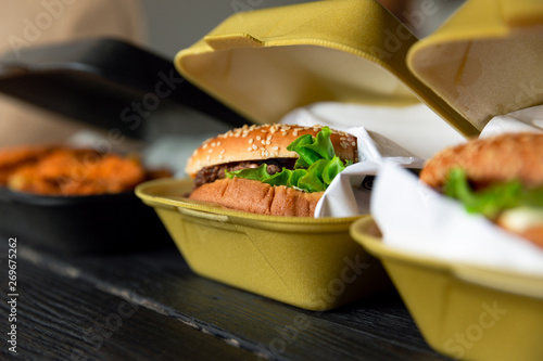 Fototapeta Hamburger in a takeaway container on the wooden background