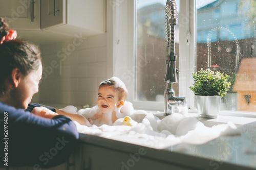 Baby having a bath in the kitchen sink Fototapet