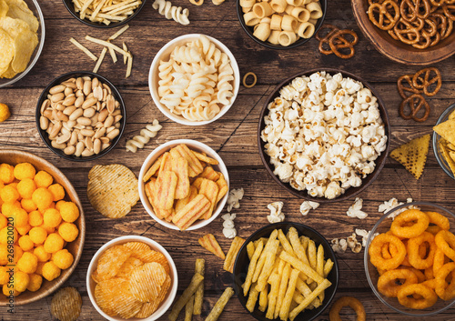 Canvas Print All classic potato snacks with peanuts, popcorn and onion rings and salted pretzels in bowl plates on wooden background