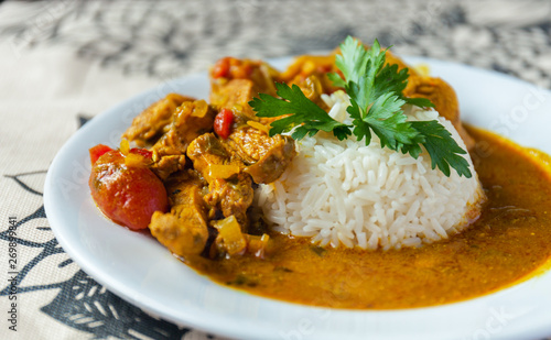 Valokuva Curry chicken bright juicy with white rice on plate over the tablecloth background