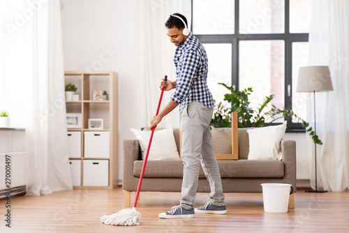 Obraz na płótnie household, housework and people concept - happy indian man in headphones with mo
