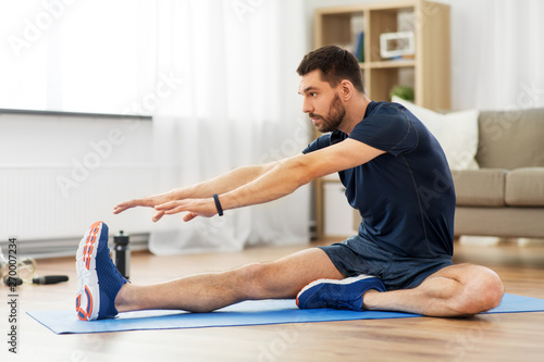 Fotografia sport, fitness and healthy lifestyle concept - man stretching leg on exercise ma