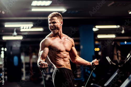 Fotografia Hard working well built sportsman exercising with a resistance band in gym