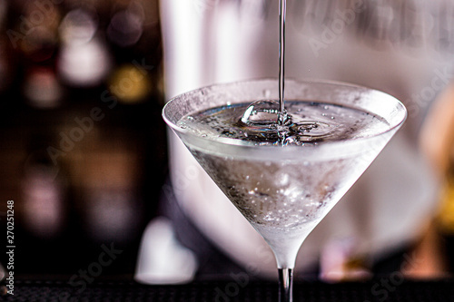 Fotografia vodka martini isolated on a black background with an olive splashing and air bub