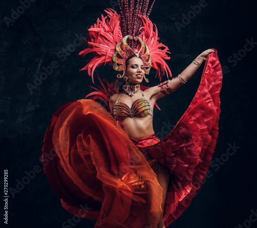 Photographie Talented joyful can can dancer in red feather costume is posing at small dark studio