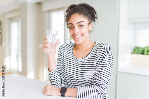 Fotomural Young african american girl drinking a fresh glass of water with a happy face st