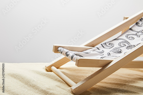 Fényképezés wooden deck chair on sand on grey background with copy space