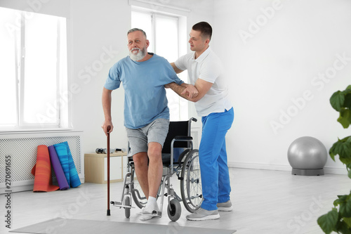 Photo Professional physiotherapist working with senior patient in rehabilitation cente