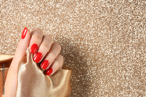 Canvas Print Woman showing manicured hand with red nail polish on color background, top view