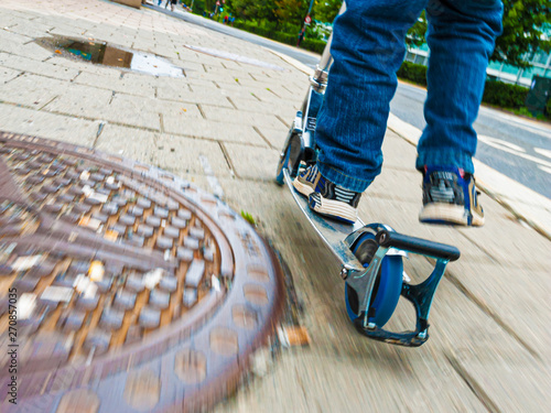 Photo Person on a kickbike passing a rusty manhole cover.