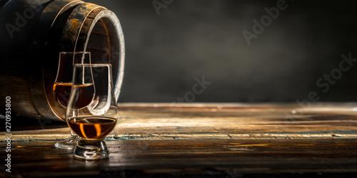 Two glasses of whiskey standing against an oak barrel Fototapeta