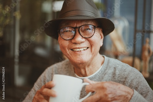 Tableau sur Toile Portrait of senior man drinking coffee in cafe